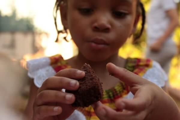 Bambina che mangia un dolcetto